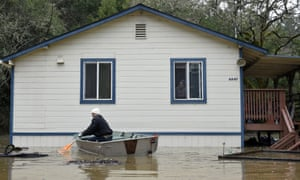 A man paddles a boat near a home surrounded by flood waters from the Russian river in Forestville, California.