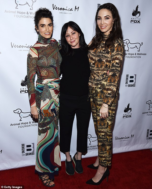 On her tippy toes: Doherty pushed up to stand next to Nikki Reed, left, and Whitney Cummings, right, at the event